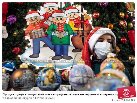 Продавщица в защитной маске продает елочные игрушки во время предпраздничные распродажи новогодних товаров в Главном универсальном магазине (ГУМ) в центре города Москвы в период пандемии короновирусной инфекции в России. Редакционное фото, фотограф Николай Винокуров / Фотобанк Лори