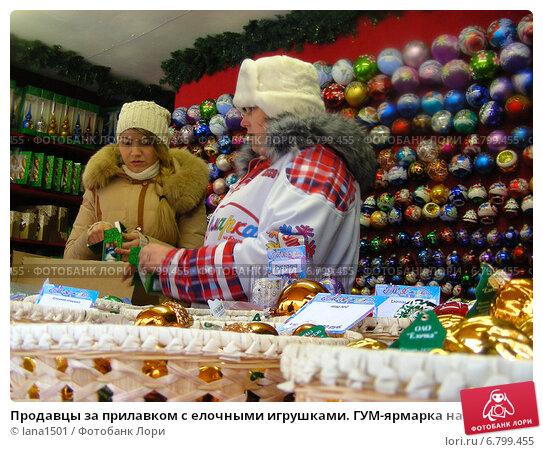Купить «Продавцы за прилавком с елочными игрушками. ГУМ-ярмарка на Красной площади в Москве», эксклюзивное фото № 6799455, снято 12 декабря 2014 г. (c) lana1501 / Фотобанк Лори