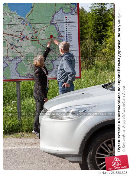 Купить «Путешествие на автомобиле по европейским дорогам, пара у информационного щита с картой дорог», фото № 26588323, снято 16 июня 2017 г. (c) Кекяляйнен Андрей / Фотобанк Лори