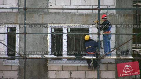 Купить «Рабочие устанавливают окна в строящемся доме», видеоролик № 3560867, снято 16 апреля 2009 г. (c) Losevsky Pavel / Фотобанк Лори
