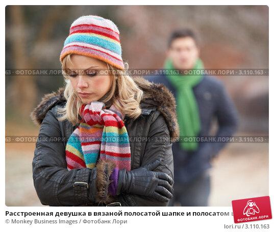Купить «Расстроенная девушка в вязаной полосатой шапке и полосатом шарфе, мужчина на заднем плане», фото № 3110163, снято 7 декабря 2010 г. (c) Monkey Business Images / Фотобанк Лори