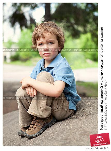 Купить «Расстроенный одинокий мальчик сидит в парке на камне», фото № 4042051, снято 6 июня 2012 г. (c) Римма Зайцева / Фотобанк Лори
