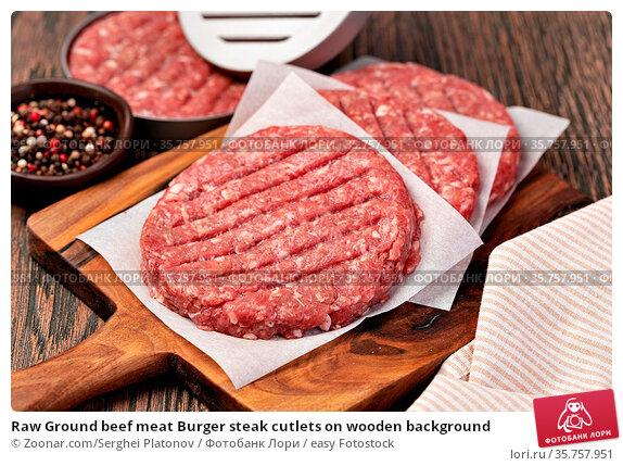 Raw Ground beef meat Burger steak cutlets on wooden background. Стоковое фото, фотограф Zoonar.com/Serghei Platonov / easy Fotostock / Фотобанк Лори