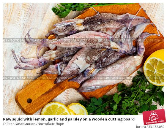 Купить «Raw squid with lemon, garlic and parsley on a wooden cutting board», фото № 33132039, снято 6 апреля 2020 г. (c) Яков Филимонов / Фотобанк Лори
