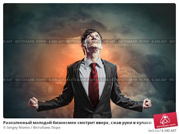 Купить «Разозленный молодой бизнесмен смотрит вверх, сжав руки в кулаки», фото № 4340447, снято 27 ноября 2012 г. (c) Sergey Nivens / Фотобанк Лори