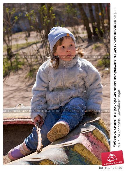 Ребенок сидит на раскрашенной покрышке на детской площадке ранней весной, фото № 127107, снято 29 апреля 2007 г. (c) Ольга Сапегина / Фотобанк Лори