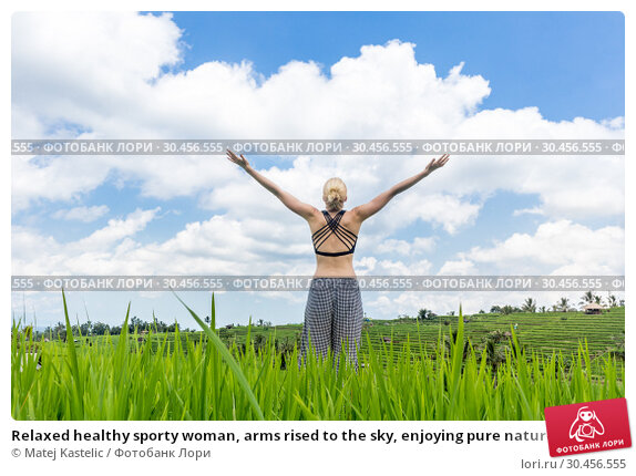 Relaxed healthy sporty woman, arms rised to the sky, enjoying pure nature at beautiful green rice fields on Bali. Стоковое фото, фотограф Matej Kastelic / Фотобанк Лори