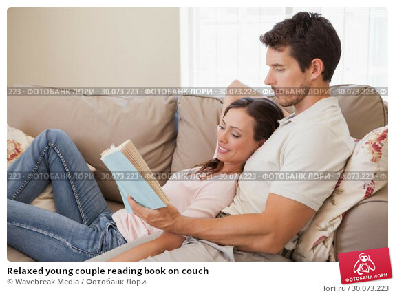 Купить «Relaxed young couple reading book on couch», фото № 30073223, снято 12 декабря 2013 г. (c) Wavebreak Media / Фотобанк Лори