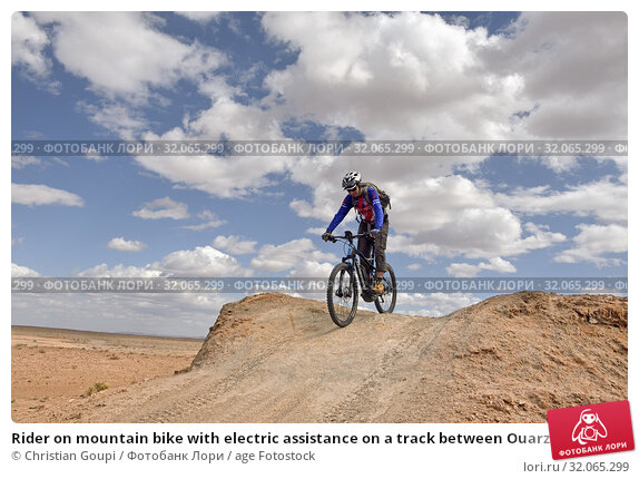 Rider on mountain bike with electric assistance on a track between Ouarzazate and Ait Ben Haddou, , Ounila River valley, Ouarzazate Province, region of Draa-Tafilalet, Morocco, North West Africa. (2019 год). Редакционное фото, фотограф Christian Goupi / age Fotostock / Фотобанк Лори