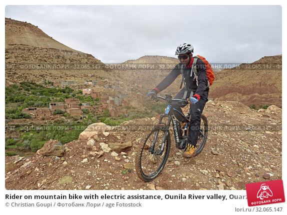 Rider on mountain bike with electric assistance, Ounila River valley, Ouarzazate Province, region of Draa-Tafilalet, Morocco, North West Africa. (2019 год). Редакционное фото, фотограф Christian Goupi / age Fotostock / Фотобанк Лори