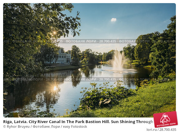 Купить «Riga, Latvia. City River Canal In The Park Bastion Hill. Sun Shining Through Green Foliage In Sunny Summer Evening. Fountains In Water Of River Canal.», фото № 28700435, снято 2 июля 2016 г. (c) easy Fotostock / Фотобанк Лори