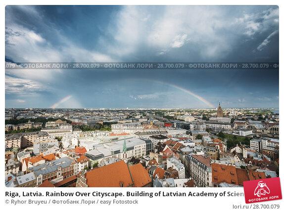 Купить «Riga, Latvia. Rainbow Over Cityscape. Building of Latvian Academy of Sciences, built on model of Moscow Stalin skyscrapers. Bureau and administration of...», фото № 28700079, снято 1 июля 2016 г. (c) easy Fotostock / Фотобанк Лори