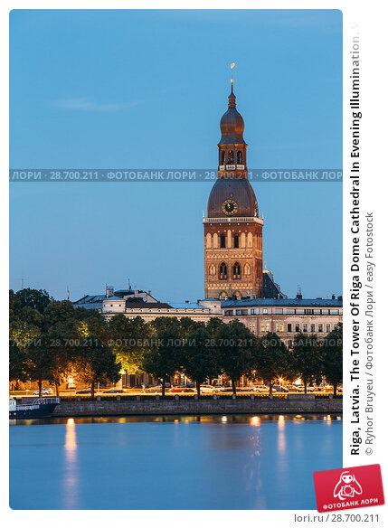 Купить «Riga, Latvia. The Tower Of Riga Dome Cathedral In Evening Illumination. View From Daugava River To Embankment And Old Town In Summer Dusk Under Blue Sky.», фото № 28700211, снято 30 июня 2016 г. (c) easy Fotostock / Фотобанк Лори