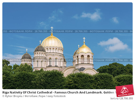 Купить «Riga Nativity Of Christ Cathedral - Famous Church And Landmark. Golden Yellow Domes On Blue Sunny Sky Background At Summer Season.», фото № 28700355, снято 1 июля 2016 г. (c) easy Fotostock / Фотобанк Лори
