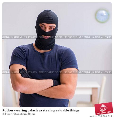 Robber wearing balaclava stealing valuable things. Стоковое фото, фотограф Elnur / Фотобанк Лори