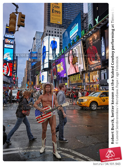 Robert Burck, better known as the Naked Cowboy performing at Times Square at dusk. Manhattan, New York City, USA. Редакционное фото, фотограф Leonid Serebrennikov / age Fotostock / Фотобанк Лори