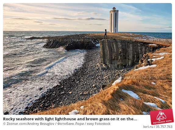 Rocky seashore with light lighthouse and brown grass on it on the... Стоковое фото, фотограф Zoonar.com/Andrey Bezuglov / easy Fotostock / Фотобанк Лори