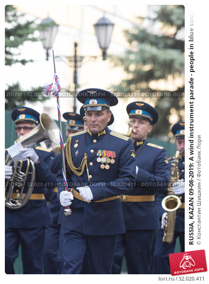 Купить «RUSSIA, KAZAN 09-08-2019: A wind instrument parade - people in blue costumes walking on the street holding musical instruments», фото № 32020411, снято 9 августа 2019 г. (c) Константин Шишкин / Фотобанк Лори
