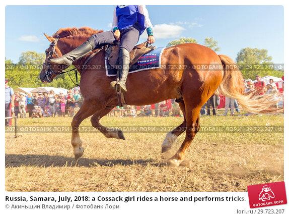 Купить «Russia, Samara, July, 2018: a Cossack girl rides a horse and performs tricks.», фото № 29723207, снято 29 июля 2018 г. (c) Акиньшин Владимир / Фотобанк Лори