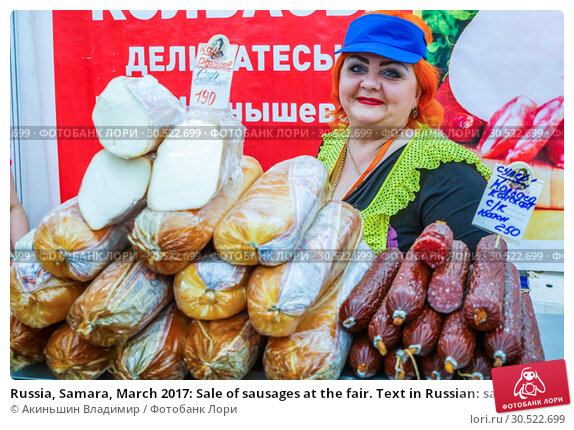 Russia, Samara, March 2017: Sale of sausages at the fair. Text in Russian: sausages delicacies. Редакционное фото, фотограф Акиньшин Владимир / Фотобанк Лори
