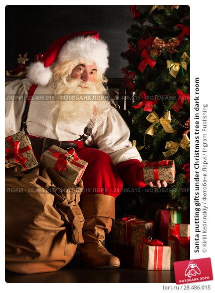 Купить «Santa putting gifts under Christmas tree in dark room», фото № 28486015, снято 31 января 2013 г. (c) Ingram Publishing / Фотобанк Лори