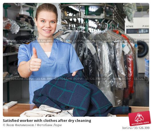 Купить «Satisfied worker with clothes after dry cleaning», фото № 33126399, снято 9 мая 2018 г. (c) Яков Филимонов / Фотобанк Лори