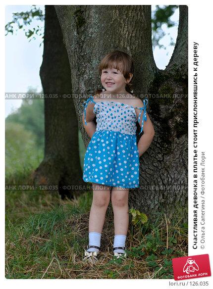 Счастливая девочка в платье стоит прислонившись к дереву, фото № 126035, снято 22 августа 2007 г. (c) Ольга Сапегина / Фотобанк Лори