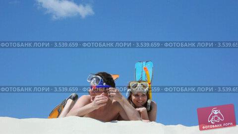 Купить «Счастливая пара пловцов лежит на песке», видеоролик № 3539659, снято 26 марта 2010 г. (c) Losevsky Pavel / Фотобанк Лори