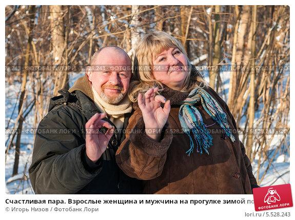 """Купить «Счастливая пара. Взрослые женщина и мужчина на прогулке зимой показывают что всё будет """"окей!""""», эксклюзивное фото № 5528243, снято 25 января 2014 г. (c) Игорь Низов / Фотобанк Лори"""