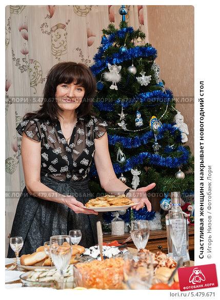 Купить «Счастливая женщина накрывает новогодний стол», эксклюзивное фото № 5479671, снято 7 января 2014 г. (c) Игорь Низов / Фотобанк Лори