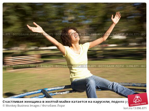 Купить «Счастливая женщина в желтой майке катается на карусели, подняв руки вверх», фото № 3096871, снято 28 февраля 2010 г. (c) Monkey Business Images / Фотобанк Лори