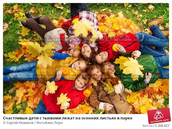 Купить «Счастливые дети с тыквами лежат на осенних листьях в парке», фото № 5308827, снято 6 октября 2013 г. (c) Сергей Новиков / Фотобанк Лори