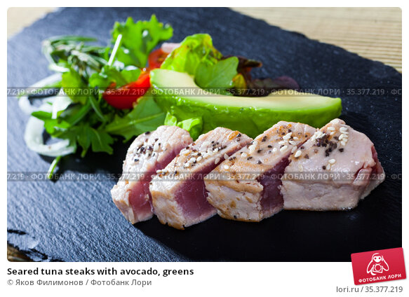 Seared tuna steaks with avocado, greens. Стоковое фото, фотограф Яков Филимонов / Фотобанк Лори