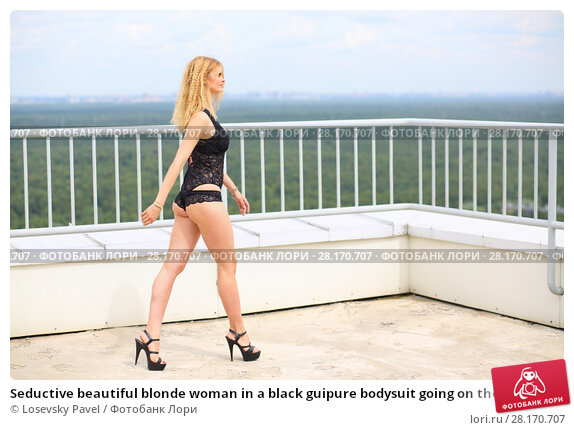 Купить «Seductive beautiful blonde woman in a black guipure bodysuit going on the roof of a multistory building against the cloudy sky and forest», фото № 28170707, снято 30 июля 2015 г. (c) Losevsky Pavel / Фотобанк Лори