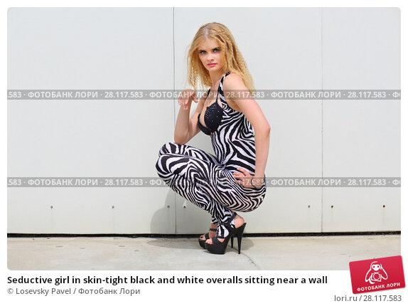 Купить «Seductive girl in skin-tight black and white overalls sitting near a wall», фото № 28117583, снято 30 июля 2015 г. (c) Losevsky Pavel / Фотобанк Лори