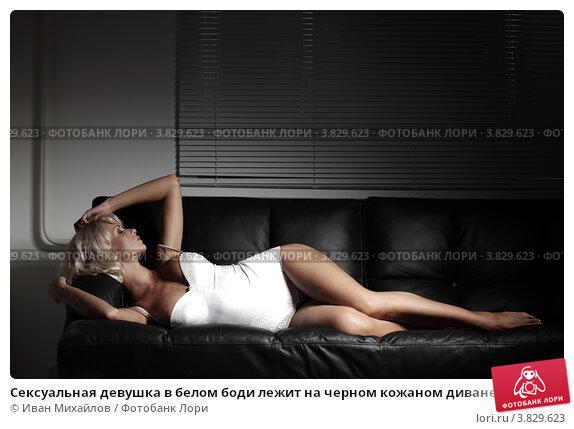 Грудастая девушка в черном боди мастурбирует на кожаном диване