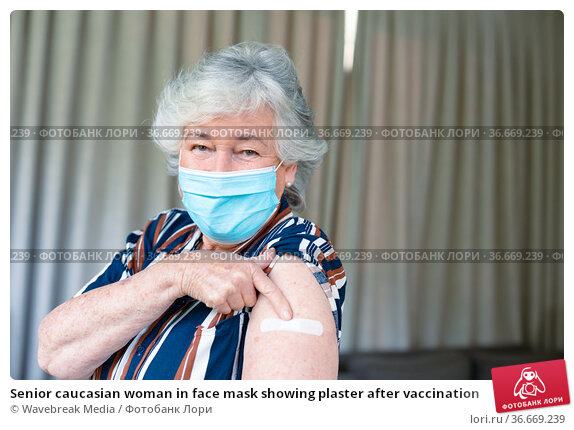 Senior caucasian woman in face mask showing plaster after vaccination. Стоковое фото, агентство Wavebreak Media / Фотобанк Лори