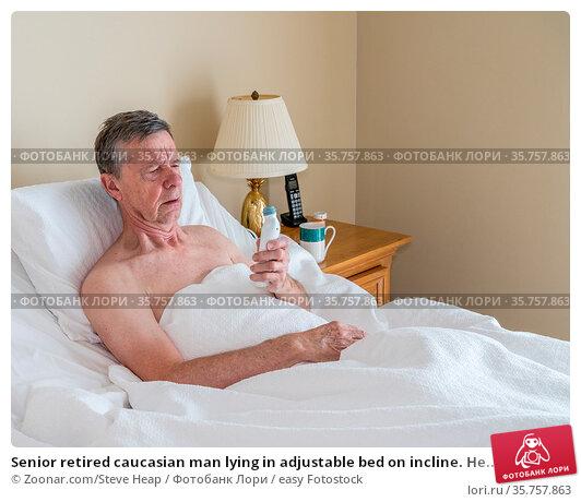 Senior retired caucasian man lying in adjustable bed on incline. He... Стоковое фото, фотограф Zoonar.com/Steve Heap / easy Fotostock / Фотобанк Лори