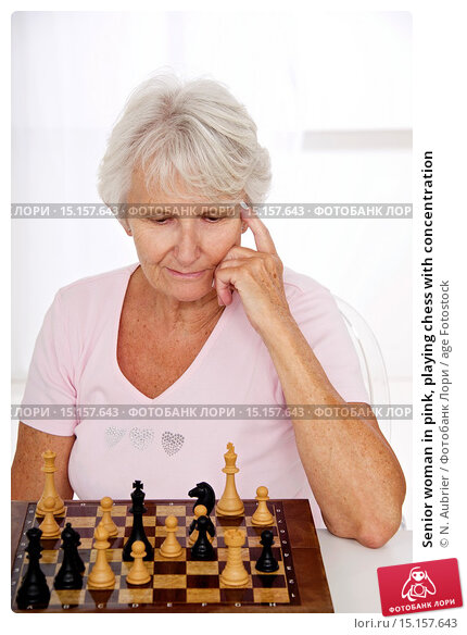 Купить «Senior woman in pink, playing chess with concentration», фото № 15157643, снято 17 октября 2014 г. (c) age Fotostock / Фотобанк Лори