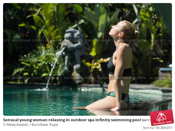 Купить «Sensual young woman relaxing in outdoor spa infinity swimming pool surrounded with lush tropical greenery of Ubud, Bali.», фото № 30369011, снято 22 февраля 2019 г. (c) Matej Kastelic / Фотобанк Лори