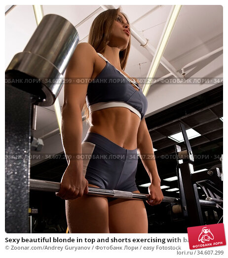 Sexy beautiful blonde in top and shorts exercising with barbell shot... Стоковое фото, фотограф Zoonar.com/Andrey Guryanov / easy Fotostock / Фотобанк Лори