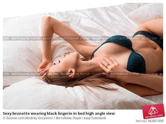 Sexy brunette wearing black lingerie in bed high angle view. Стоковое фото, фотограф Zoonar.com/Andrey Guryanov / easy Fotostock / Фотобанк Лори