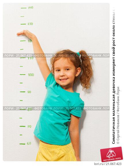 Купить «Симпатичная маленькая девочка измеряет свой рост около стены с отметками», фото № 21067423, снято 12 декабря 2015 г. (c) Сергей Новиков / Фотобанк Лори