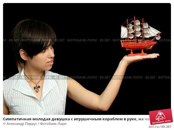 Симпатичная молодая девушка с игрушечным кораблем в руке, на черном фоне, фото № 89387, снято 31 мая 2007 г. (c) Александр Паррус / Фотобанк Лори
