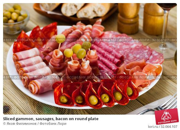 Sliced gammon, sausages, bacon on round plate. Стоковое фото, фотограф Яков Филимонов / Фотобанк Лори