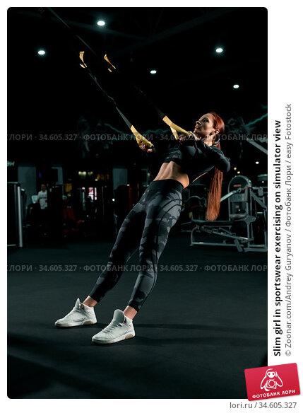 Slim girl in sportswear exercising on simulator view. Стоковое фото, фотограф Zoonar.com/Andrey Guryanov / easy Fotostock / Фотобанк Лори