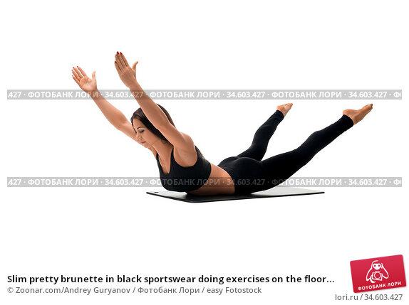 Slim pretty brunette in black sportswear doing exercises on the floor... Стоковое фото, фотограф Zoonar.com/Andrey Guryanov / easy Fotostock / Фотобанк Лори