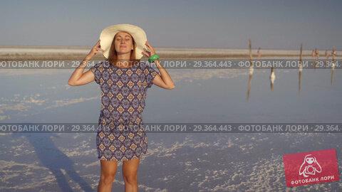 Купить «Slim sexy girl in white hat enjoying sunset, wooden salt pillars of a salt lake», видеоролик № 29364443, снято 28 октября 2018 г. (c) Ирина Мойсеева / Фотобанк Лори