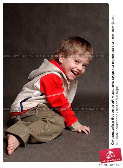 Смеющийся босоногий мальчик сидя на коленях на темном фоне, фото № 303739, снято 23 марта 2008 г. (c) Юлия Кашкарова / Фотобанк Лори