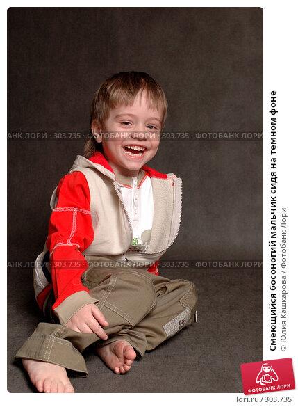 Купить «Смеющийся босоногий мальчик сидя на темном фоне», фото № 303735, снято 23 марта 2008 г. (c) Юлия Кашкарова / Фотобанк Лори